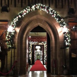 Warwick Castle walkway with lit garlands around the arches