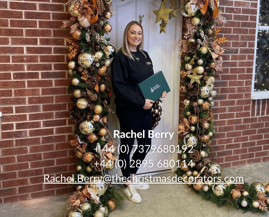 Lady at a front door of a house surrounded by Christmas decorations